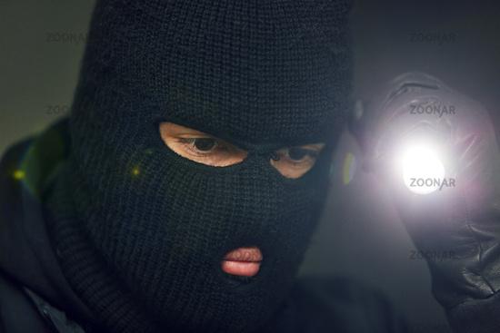 Einbrecher oder Dieb sucht mit Taschenlampe