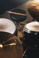 Closeup view of a drum set and Drumsticks in a dark studio. Black drum barrels with chrome trim. The concept of live performances