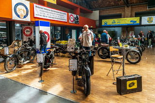 Various vintage motorcycles stand in a row.