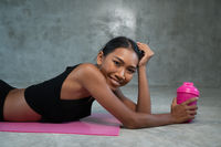 Happy healthy smiling woman holding protein shake relaxing on the pink yoga mat at the gym