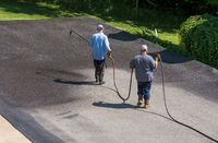 Workers spraying blacktop or asphalt sealer onto roadway
