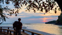 Traveler looking at the sunset on Tarutao island, Thailand