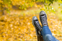 Teenage girl with sneakers is lying on bench closeup