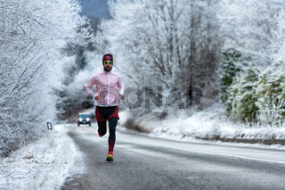 Young runner on ice cold road on the Alps