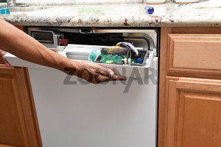 Closeup of a appliance repairman removing the control panel to a broken dishwasher
