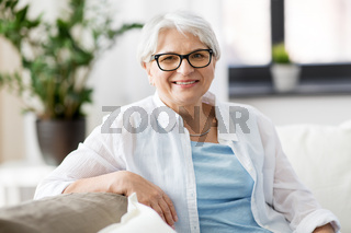 portrait of happy senior woman in glasses at home