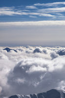 Snowy mountains covered with beautiful sunlight clouds