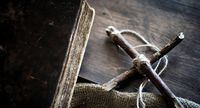 Religious old book on a wooden table. A religious cross tied wit
