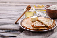 French crepes with butter flour and honey in ceramic dish on wooden kitchen table