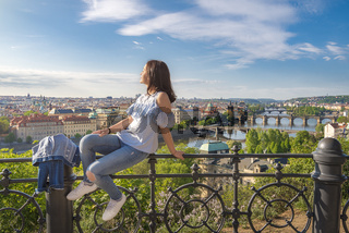 Woman on a fence and panorama of Prague City