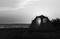 Camping tent on sea beach at sunset in summer