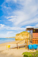 wooden beach hut and chairs on deserted beach
