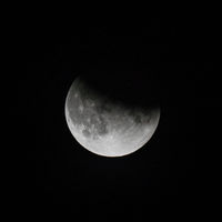 close up view of a partial lunar eclipse in the black night sky