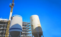 mortar silos at construction site with crane and blue sky