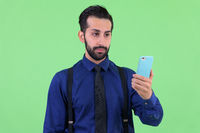 Young handsome bearded Persian businessman using phone