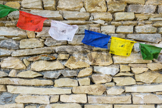 Prayer flags on stone wall