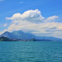 Turquoise Lake Thun. Mount Stockhorn surrounded by clouds. Village Spiez. Bernese Oberland, Switzerl