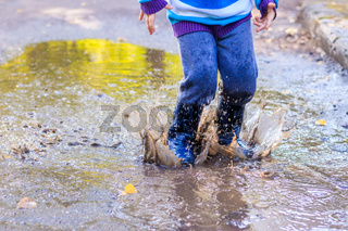 A little boy is jumping in a puddle. A boy in rubber boots. Happy childhood. Puddles after the rain. Warm summer evening.