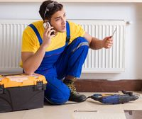 The young repairman contractor repairing heating panel