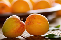 Clay dish full of ripe apricots on wooden table