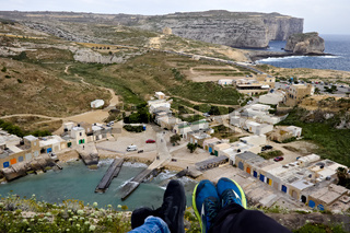 Overlooking inland sea with little houses next to it and fungus rock in the background in gozo, Malta.
