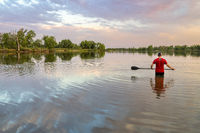 Male paddler with a long stand up paddle