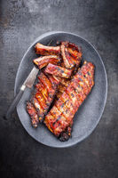 Barbecue spare ribs St Louis cut with hot honey chili marinade as top view on a modern design cast iron pan with copy space