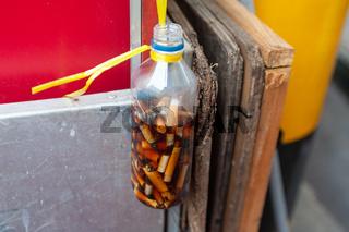 Singapur, Republik Singapur, Flasche mit Zigarettenkippen in Chinatown