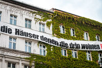 Banner on building facade with protest slogan against real estate speculation. Houses for the residents (german: Häuser , denen, die drin Wohnen)
