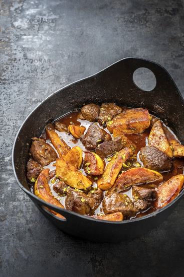 Traditional Iranian khoresh beh stew with chunks of lamb and quinces as top view in a modern style Japanese cast-iron roasting dish