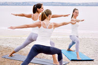 Group of women practising asana exercise Virabhadrasana Warrior Pose