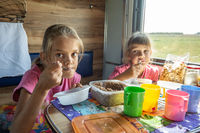 Two girls eat on the train