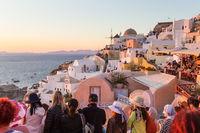 Indian tourists taking photos of colorful Oia village on Santorini island, Greece.