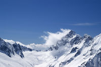 Winter snowy mountains in clouds and beautiful blue sky