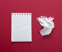 notebook with white sheets and a crumpled  sheet of paper