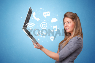 Woman holding laptop with online symbols