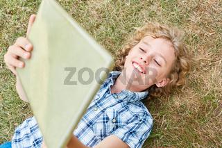 Fröhlicher Junge mit seinem Tablet Computer