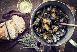 Traditional barbecue Italian blue mussel with farmhouse bread and white wine as top view in a casserole as vintage