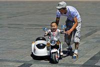 Toddler boy riding an electric toy motor-bike with the help of his father , Mongolia