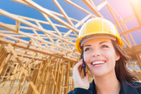 Female Contractor In Hard Hat Using Cell Phone At Construction Site