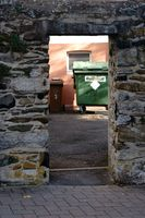 Dustbins behind wall of fieldstone