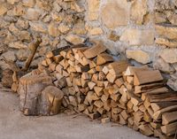 Stack of firewood against stone wall of farmhouse