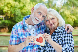 Verliebtes Senioren Paar hält ein Herz in Händen