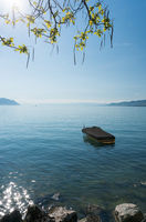 A beautiful view of Lake Geneva and surrounding mountains on a summer day with a single boat in the