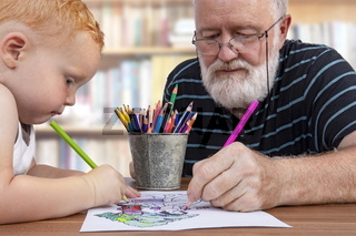 Teamwork between grandfather and grandson to color a drawing