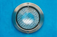 Detail of a round pool spotlight with blue background