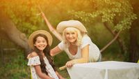 Grandmother And Granddaughter Are At The Table In The Garden2