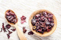 Top view at wooden bowl and spoon of dry hibiscus petals on linen cloth background