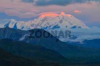 Sunrise view of Mount Denali (mt Mckinley) peak with red alpenglow from Stony Dome overlook. Denali National Park and Preserve, Alaska, United States