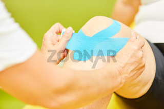Mann bekommt Kinesio Tape ans Kniegelenk